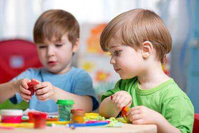 Two young children engaged in parallel play