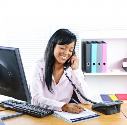 Woman sitting at desk talking on phone
